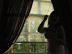 woman closing blinds and curtains